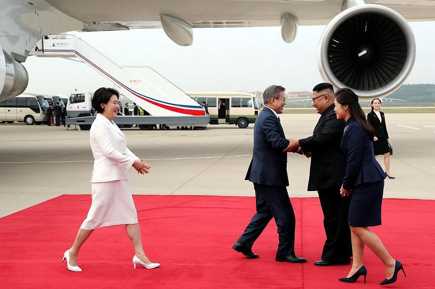 Kim Jung-sook (in white) walking to greet Ri Sol Ju on the red carpet at the Sunan International Airport in Pyongyang, on Sept 18, 2018.