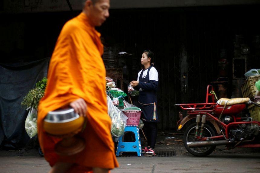 A Buddhist monk walks past a street vendor in Bangkok, Thailand, on Sept 10, 2018.
