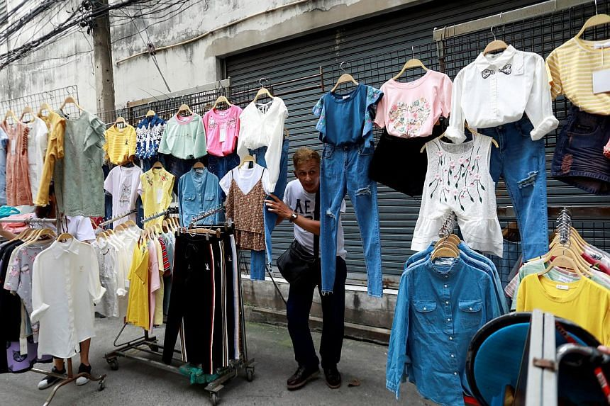 A street vendor holds his clothes when police take action on a street in Bangkok, Thailand, on Sept 12, 2018.
