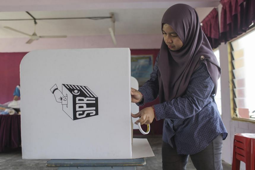 An Election Commission of Malaysia officer prepares a ballot box ahead of the 14th national general elections, on May 9, 2018.