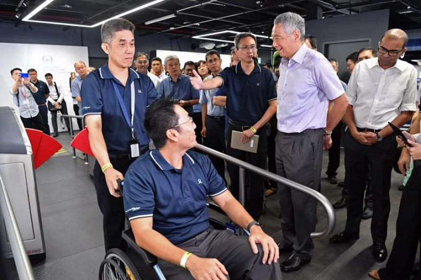 Prime Minister Lee Hsien Loong (second right) and Senior Minister of State for Transport Dr Janil Puthucheary (right) view a demonstration of a gantry for disabled passengers at the  official launch of the SG Mobility Gallery.