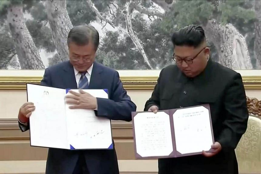 South Korean President Moon Jae-in and North Korean leader Kim Jong Un display their signed documents during the inter-Korean summit at the Paekhwawon State Guesthouse in Pyongyang, on Sept 19, 2018.