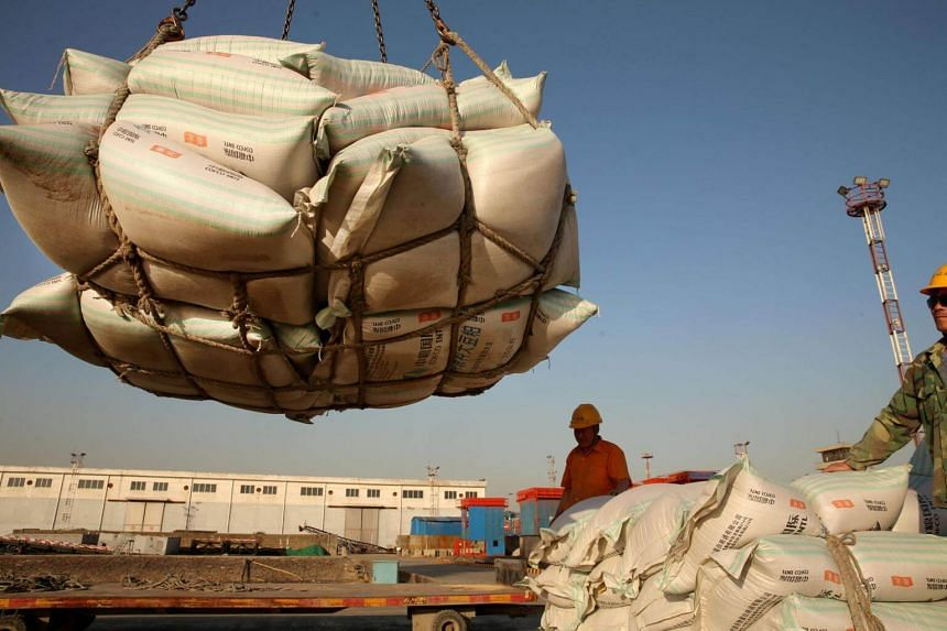 Workers transport imported soybean products at a port in Nantong, Jiangsu province, China, on April 9, 2018.