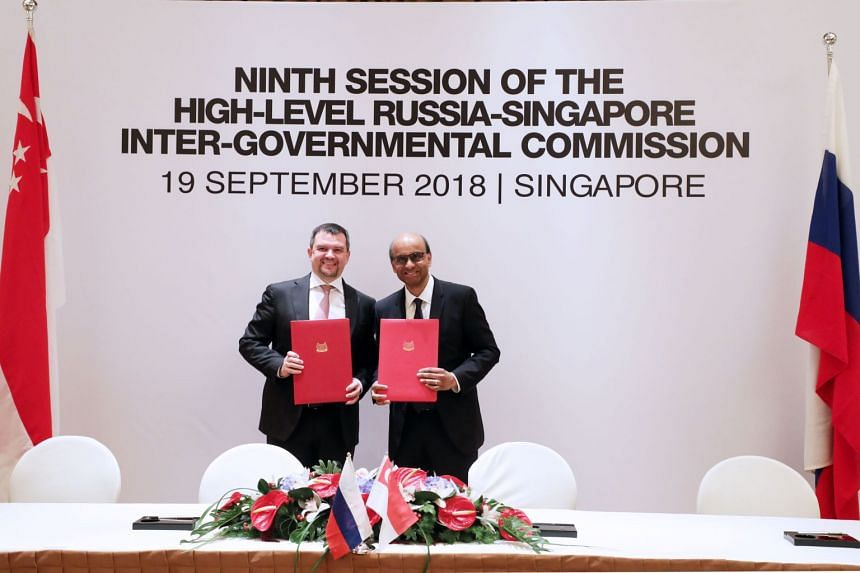 Singapore's Deputy Prime Minister Tharman Shanmugaratnam and Russia's Deputy Prime Minister Maxim Akimov holding up the signed Joint Statement of the Ninth Session of the IGC in Singapore, on Sept 19, 2018.