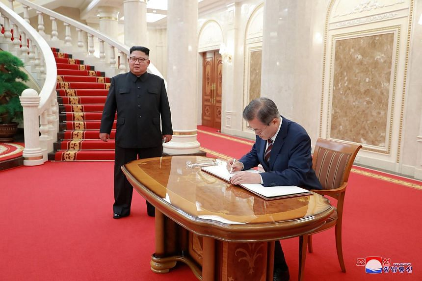 South Korean President Moon Jae-in signs a guestbook as North Korean leader Kim Jong Un looks on at the headquarters of the Central Committee of the Workers' Party of Korea in Pyongyang.