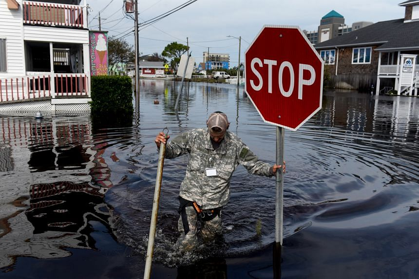 A member of a critical crisis search and rescue team wading through floodwaters in Carolina Beach, North Carolina, on Monday. At least 32 people have been killed since Florence came ashore as a hurricane last Friday. Widespread flooding has reached r