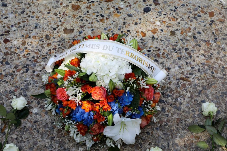 """A bouquet reading """"for the victims of terrorism"""" lies in front of a memorial fountain during a national ceremony to pay tribute to the victims of militant attacks, in Paris, on Sept 19, 2018."""