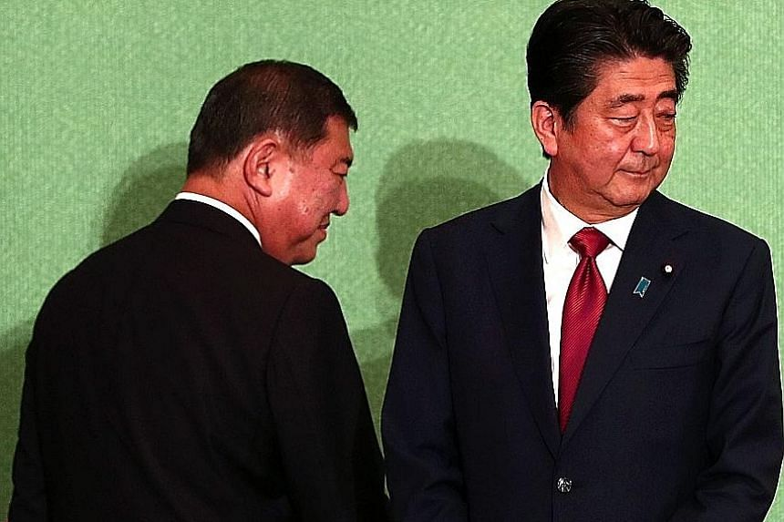 Japan's Prime Minister Shinzo Abe (right) faces former defence minister Shigeru Ishiba (left) in today's election. Mr Abe is seeking more time to amend the pacifist Constitution and pursue economic reforms.