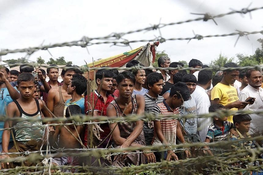 """Rohingya refugees in the """"no man's land"""" zone at the Bangladesh-Myanmar border in Rakhine State, western Myanmar, on Aug 24. The International Criminal Court's preliminary probe will look into allegations of killings, sexual violence and forced depor"""
