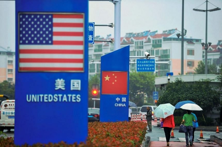 Signs with the US and Chinese flags are seen outside a store selling foreign goods in Qingdao in China's eastern Shandong province, on Sept 19, 2018.