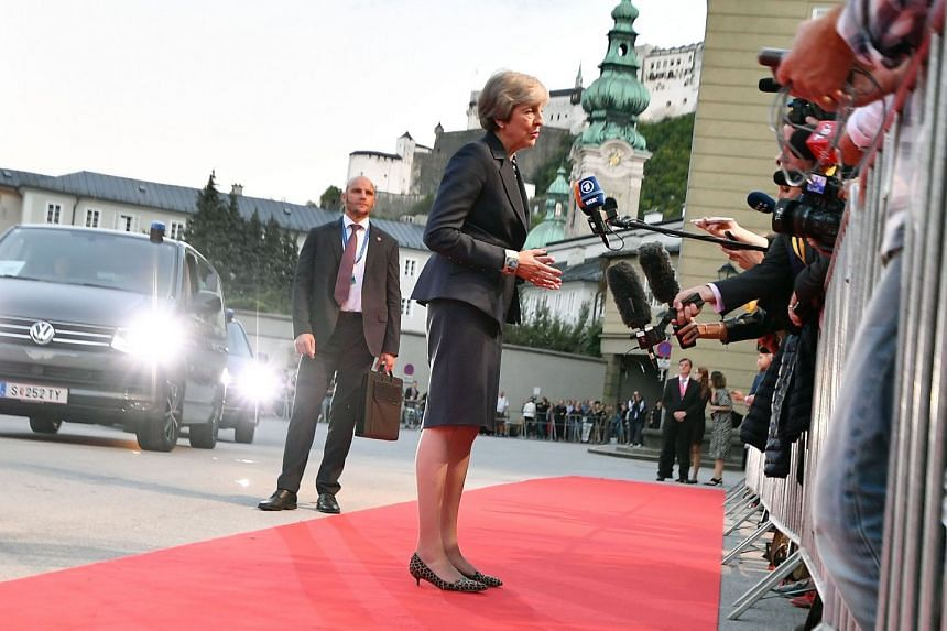 Theresa May speaks to journalists as she arrives for the informal EU summit dinner