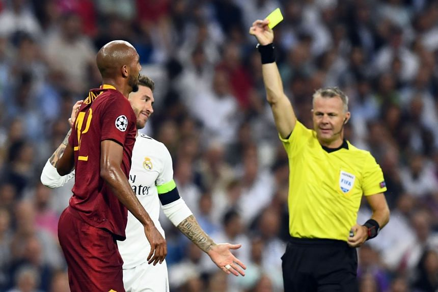 Real Madrid's Sergio Ramos (in white) is shown a yellow card by referee Bjorn Kuipers during the UEFA Champions League match against AS Roma, on Sept 19, 2018.