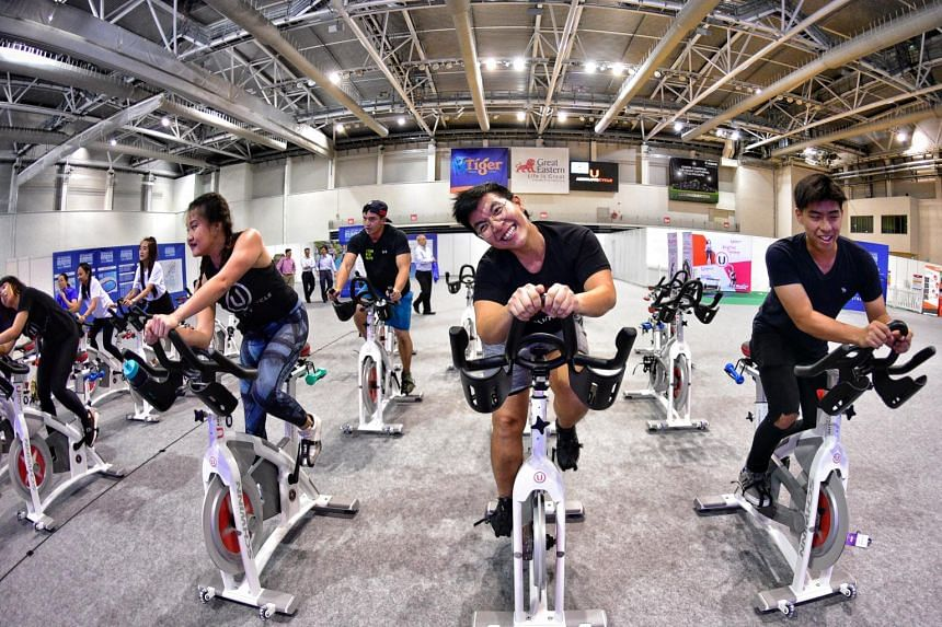 People taking part in rhythm cycling during the ST Run Festival at the OCBC Arena on Sept 20, 2018.