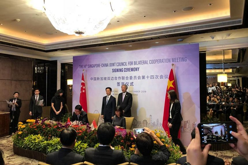 NAC chief executive Rosa Daniel (seated, right) signing a Memorandum of Understanding with Ministry of Culture and Tourism Party Leadership Group Member Du Jiang while Deputy Prime Minister Teo Chee Hean and Chinese Vice-Premier Han Zheng look on.