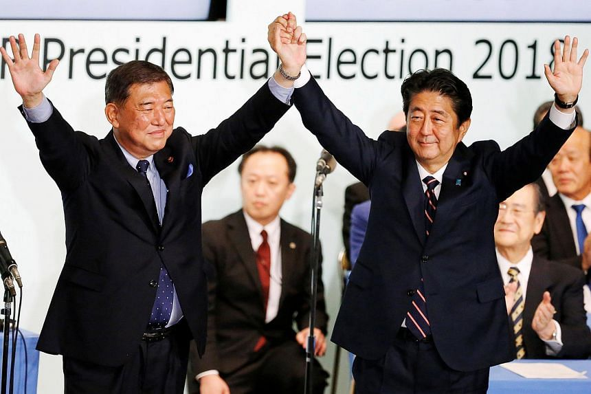 Former defence minister Shigeru Ishiba (left) raises his hands with Prime Minister Shinzo Abe who secured 553 votes against 254.