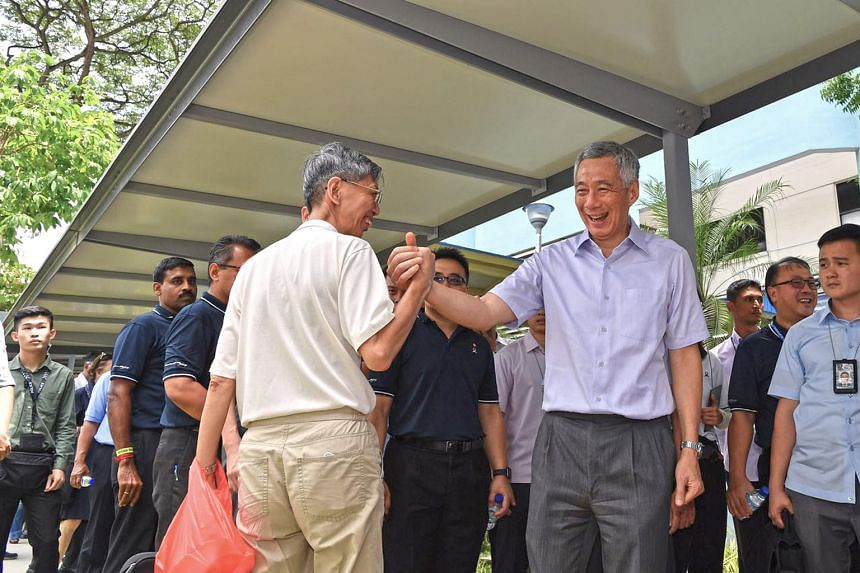 Prime Minister Lee Hsien Loong greeting a passer-by near Little India MRT station yesterday. A 150m linkway connecting the station to Tekka Market is the latest covered walkway finished under LTA's Walk2Ride scheme.