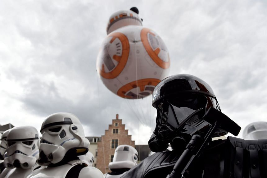 A giant balloon of Star Wars droid BB-8 floats behind participants in Star Wars costumes during an event in Belgium.