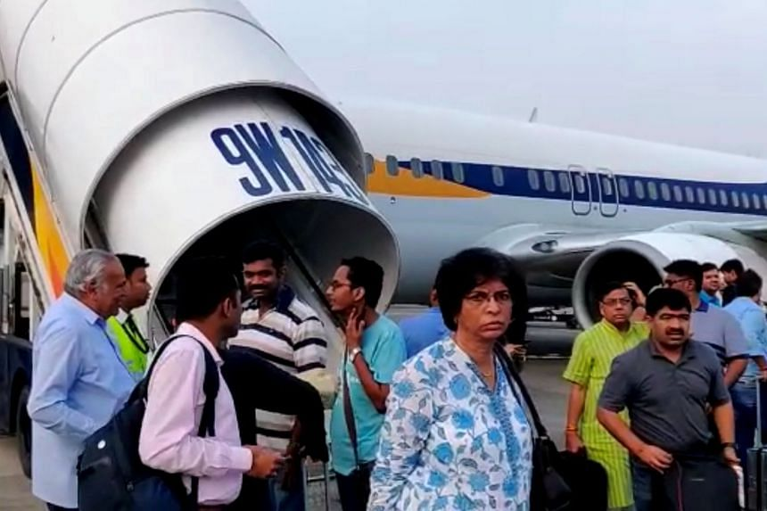 Passengers stand on the tarmac after an emergency landing, due to lost cabin pressure, on a Jet Airways flight.