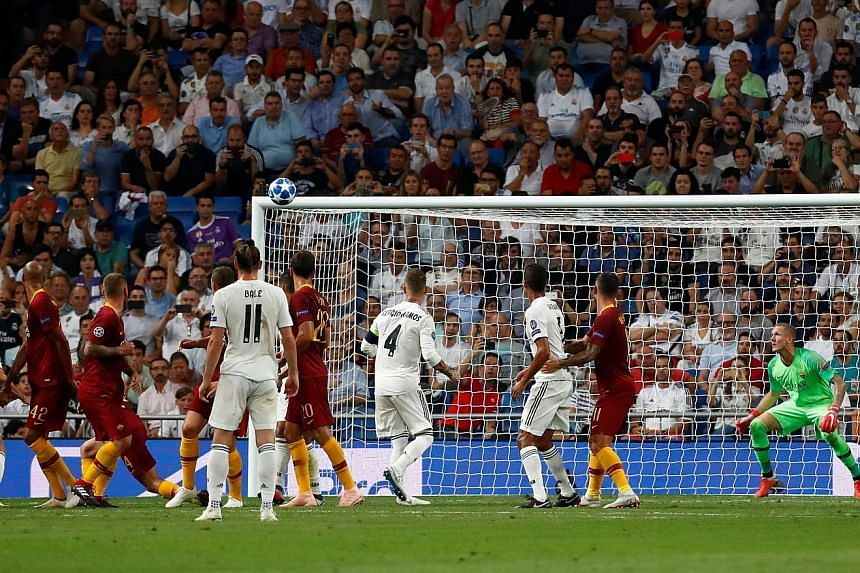 Real Madrid's Isco (not seen) curls a free kick into the top corner for the opening goal against Roma.