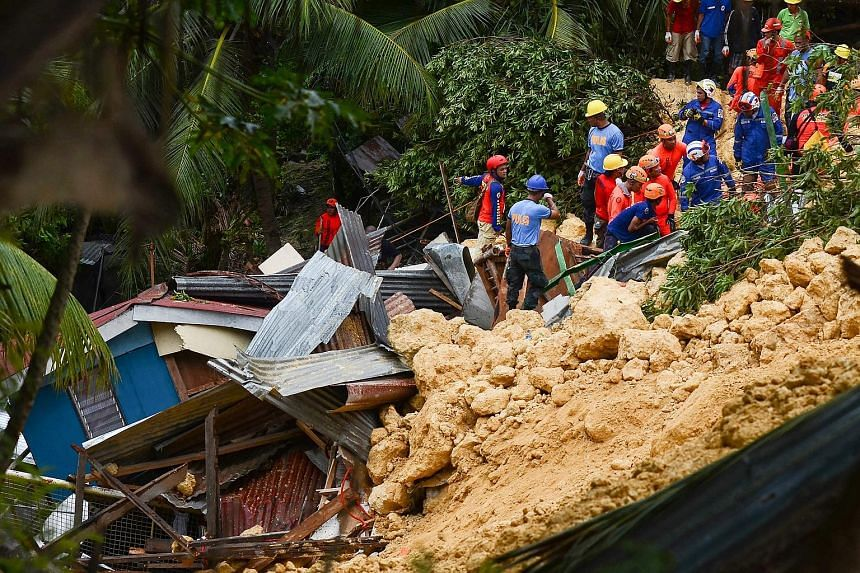 Rescuers searching for survivors at the landslide site in Naga city, on the Philippine tourist island of Cebu yesterday. Days of heavy monsoon rains caused a steep slope of crumbly limestone to collapse and crash into at least 10 homes in the early m