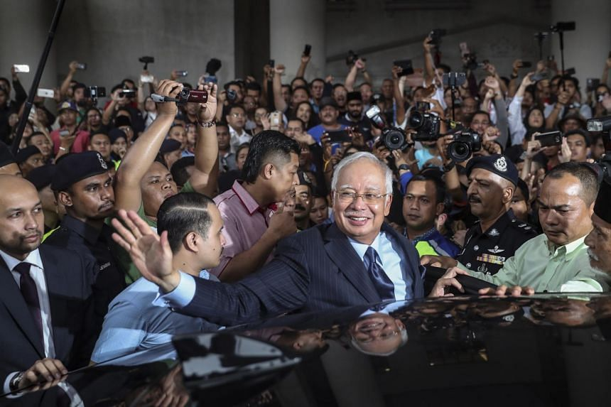 Former Malaysian Prime Minister Najib Razak (centre) waves to a supporter as he leaves the Kuala Lumpur High Court, in Malaysia, on Sept 20, 2018.