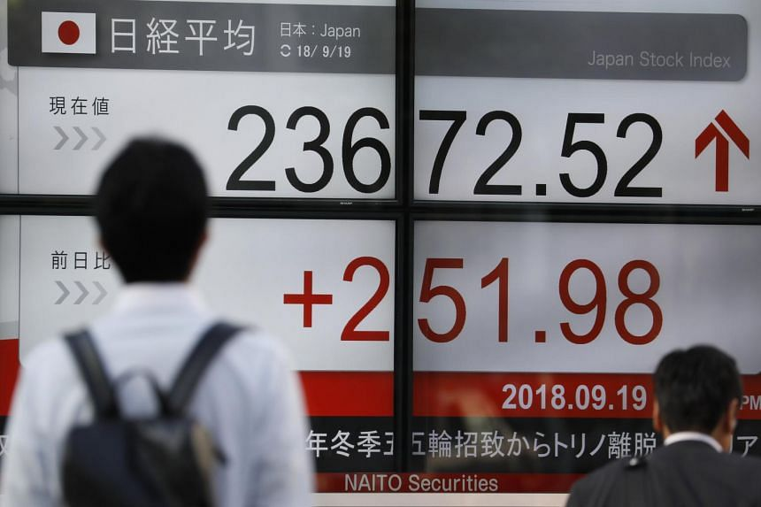 Pedestrians walk past a display showing closing information of Tokyo's stock benchmark Nikkei Stock Average in Tokyo, on Sept 19, 2018.