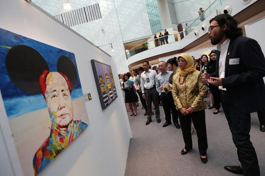 President Halimah Yacob viewing works at the Yellow Ribbon Community Art Exhibition with Singapore Art Museum's assistant curator John Tung (right) on Sept 21, 2018.