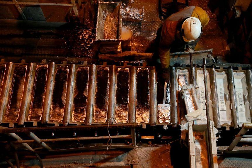 A worker controls forming of aluminium ingots on a conveyor belt at the foundry shop of the Rusal Krasnoyarsk aluminium smelter in the Siberian city of Krasnoyarsk, Russia, on Nov 9, 2017.