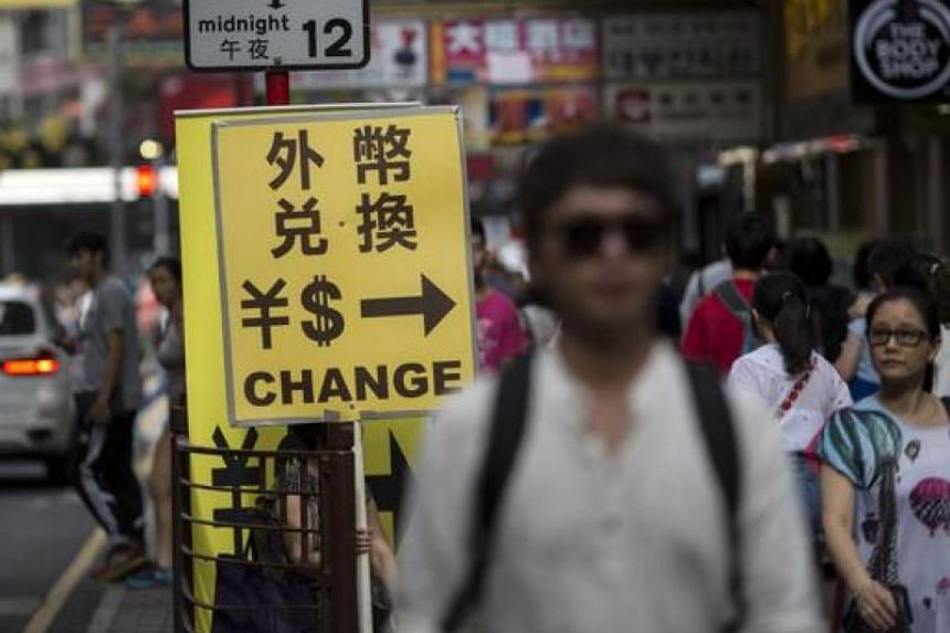 Pedestrians walk past a sign for a money exchange in Tsim Sha Tsui district, Hong Kong.