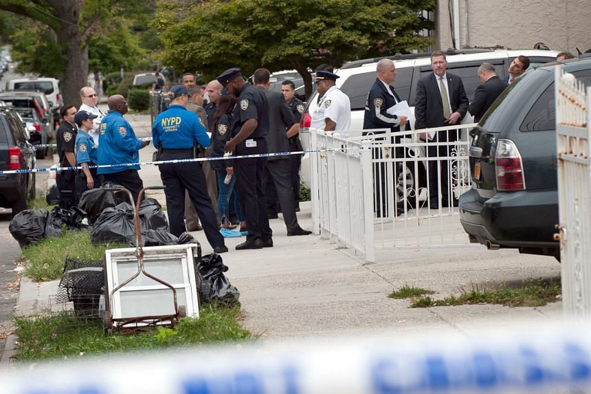 Police gather outside a daycare centre at a private home after a stabbing in the Queens borough of New York.