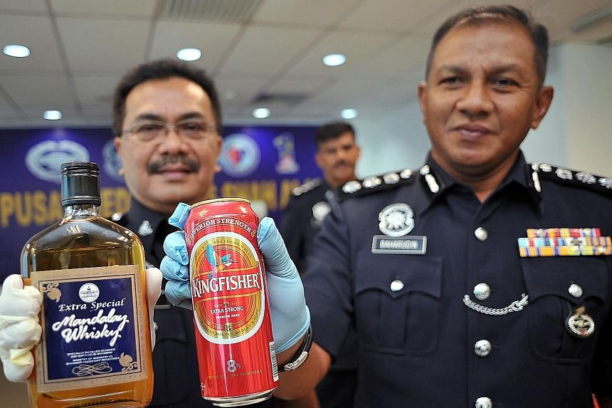 Shah Alam District Police chief Baharudin Mat Taib (right) and his deputy, Superintendent Nek Zaidi Zakaria, with two types of the illegal alcoholic drinks seized in raids in Selangor.