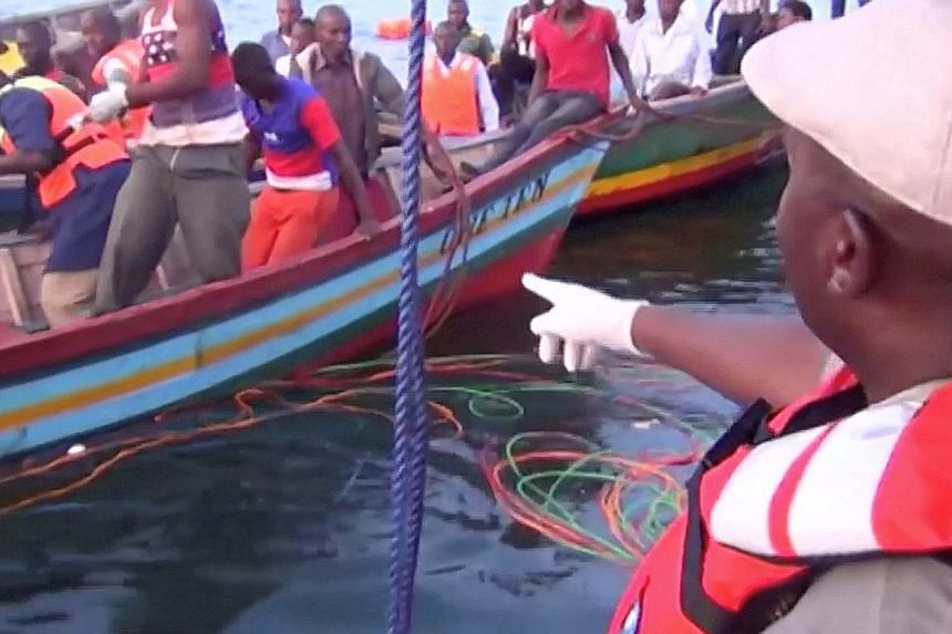 Rescue workers at the scene where a ferry overturned in Lake Victoria, Tanzania, yesterday.