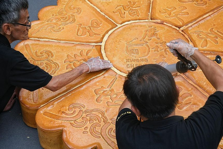 Kwong Cheong Thye factory manager Lim Poh Liang (at right, in left photo), 66, and business development executive Alvin Choo, 24, using heating devices to seal the different segments of a giant mooncake which will be unveiled today as part of the Wan