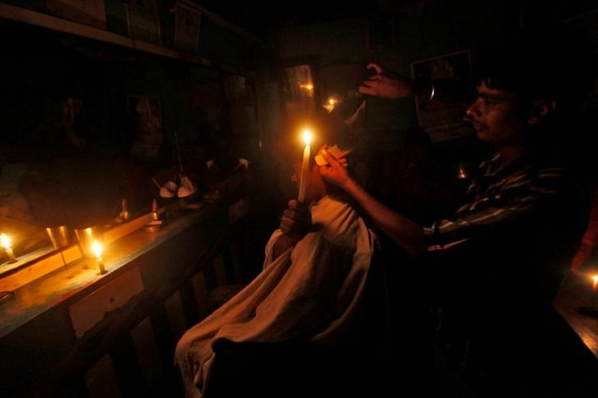 A haircut during a power-cut: A customer in Kolkata trying to give his barber enough candlelight to work by on July 31, 2012. It was during the second major blackout in as many days in India.
