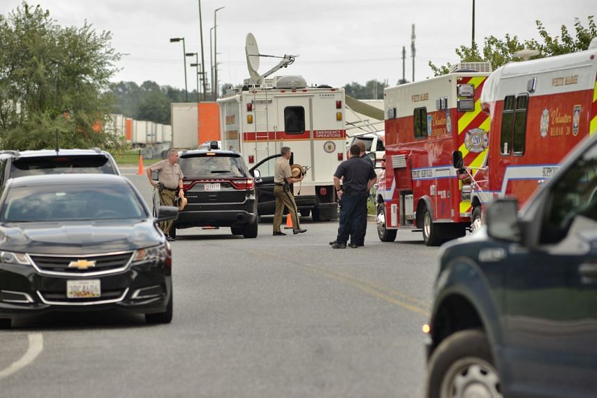 Police and emergency responders at the business park where three people were shot dead and others wounded.