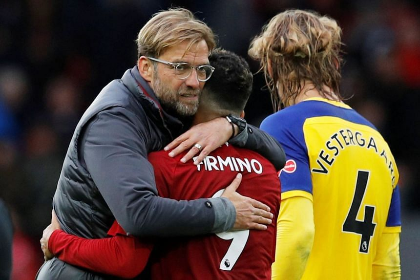 Liverpool manager Juergen Klopp and Liverpool's Roberto Firmino celebrate after the match.