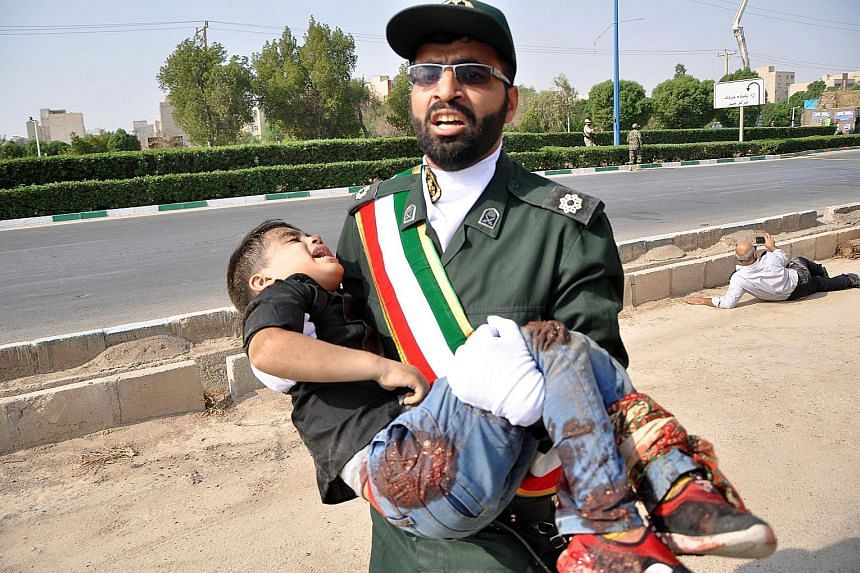 Iranian soldiers and military band members dropping to the ground during the terror attack on a military parade in the city of Ahvaz yesterday. A senior Iranian military spokesman said the attackers had hidden weapons in an area near the parade route