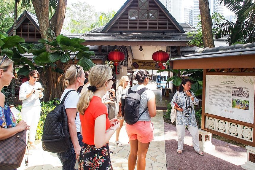 A scene from Crazy Rich Asians, which was filmed at Chijmes in Victoria Street. The nightspot is part of the itinerary for some tours based on the movie. Tourists listening to guide Catalina Tong during a visit to Newton Food Centre as part of a Craz
