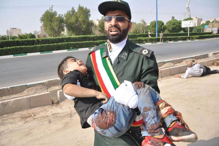 A member of Iran's Revolutionary Guards Corps carrying an injured child at the scene of an attack on a military parade, on Sept 22, 2018.