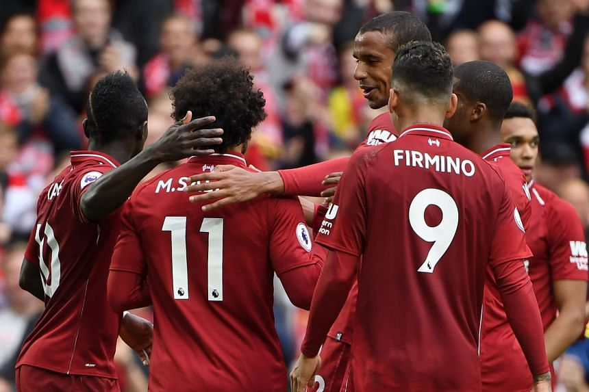 Liverpool's Egyptian midfielder Mohamed Salah (second left) celebrates scoring the team's third goal.