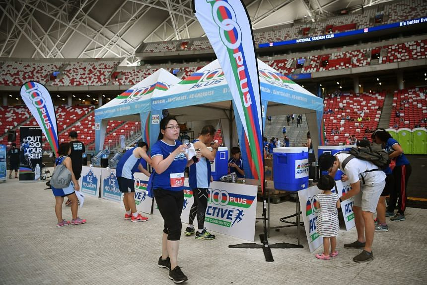 Participants getting drinks at the 100 Plus booth inside the National Stadium after their run.