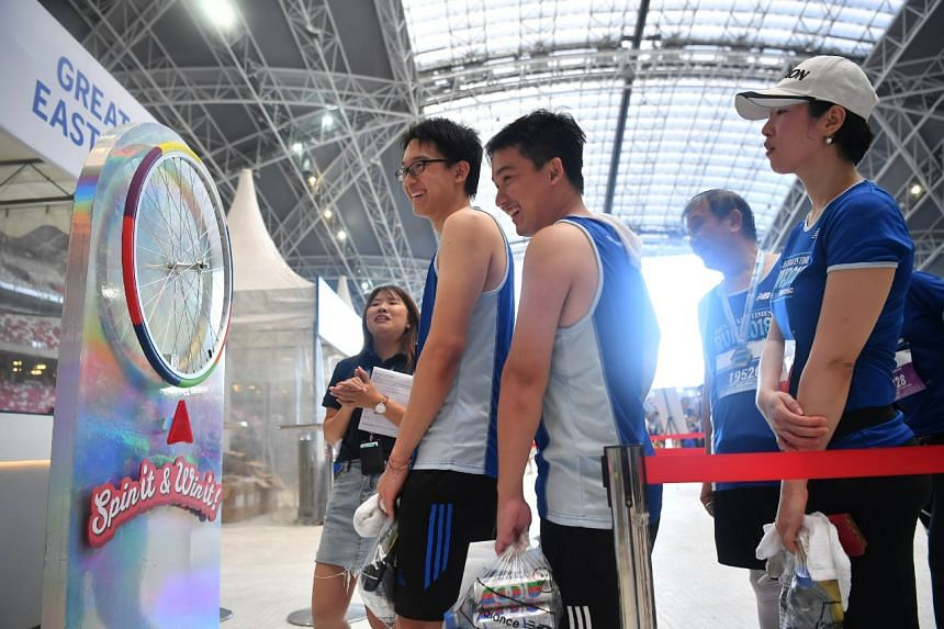 Undergraduate Nicholas Lim (second from left), 22, won a weighing scale at the Great Eastern booth after his 10km run.