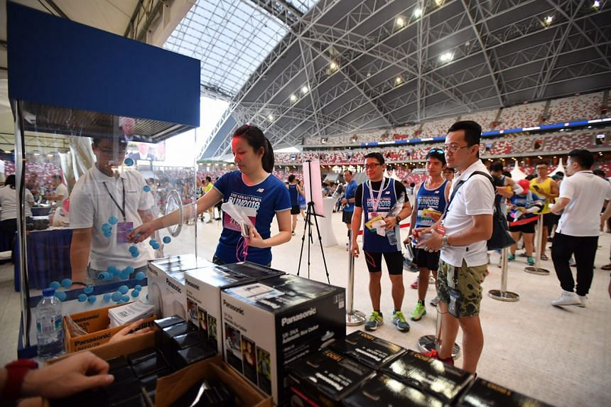 Ms Lai Kai Rou, 25, trying her luck at winning a prize at the Panasonic booth in the National Stadium after her run.