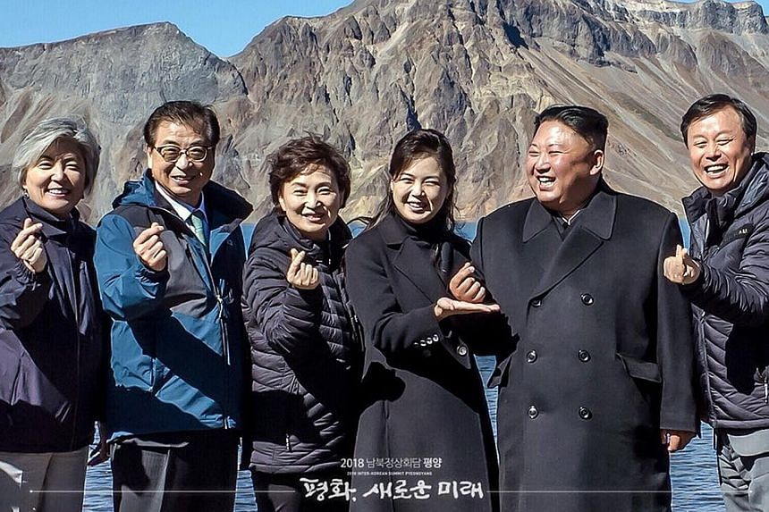 """North Korean leader Kim Jong Un (second from right), his wife, Ri Sol Ju (beside him), and South Korean officials making the so-called """"finger heart"""" gesture on top of Mount Paekdu last Thursday. Mr Kim has expressed a willingness to """"permanently"""" sc"""