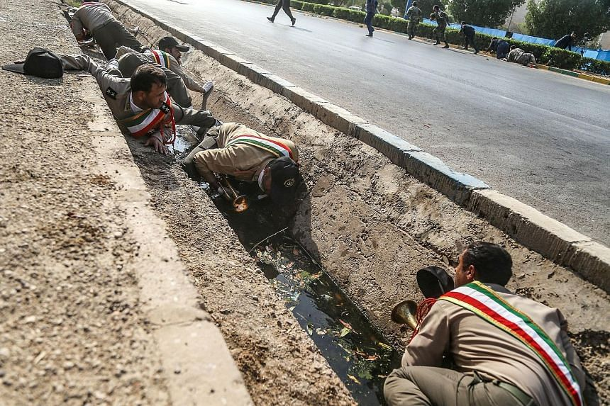 While President Hassan Rouhani (above) was delivering his speech on Saturday during an annual military parade in Teheran, an attack on another parade in Ahvaz saw Iranian soldiers taking cover in a roadside drain (below). The raid by gunmen killed 25
