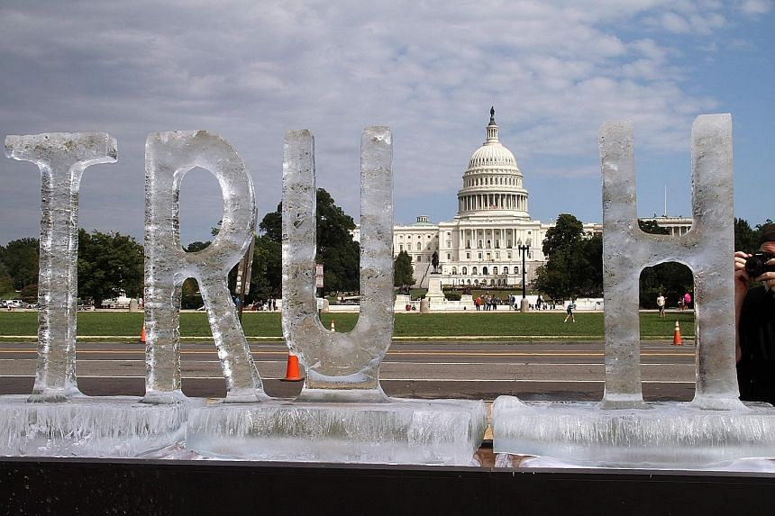 """An ice sculpture spelling the word """"truth"""" against the backdrop of the US Capitol melts slowly on a sunny day. The artwork, a poetic protest at the caustic state of politics in the era of """"fake news"""" under President Donald Trump, was installed on Sat"""