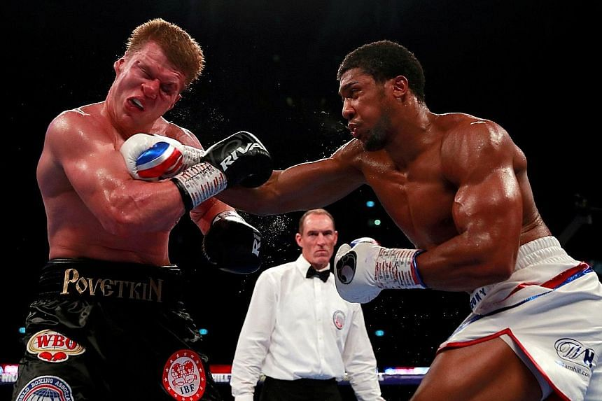 World heavyweight champion Anthony Joshua landing a punch on Alexander Povetkin's face in their fight at Wembley Stadium in London on Saturday. Joshua prevailed with a technical knockout win.