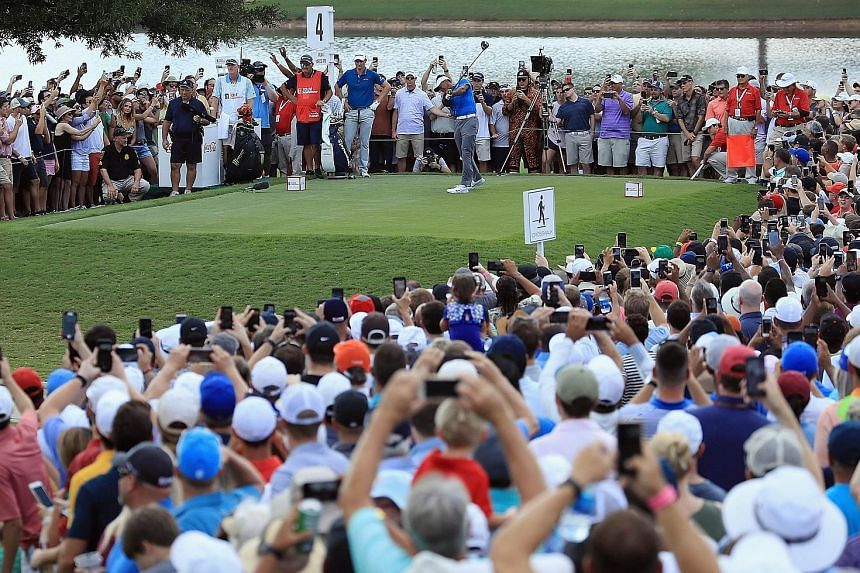 A sea of adoring supporters - and their phones - watch Tiger Woods play his shot from the fourth tee during the third round of the Tour Championship at East Lake Golf Club on Saturday.