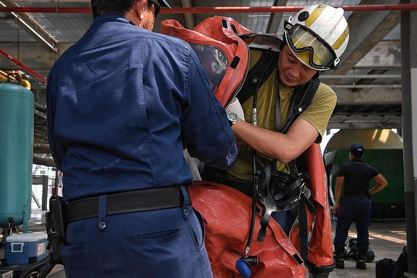 Straits Times reporter Zaihan Mohamed Yusof gets help donning a hazmat chemical suit. Weighing 24kg in total, the suit includes a breathing mask, air cylinder and a helmet.