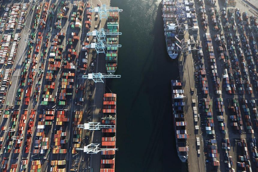 Cargo ships hold shipping containers as other containers sit at the Port of Los Angeles, on Sept 18, 2018, in San Pedro, California.